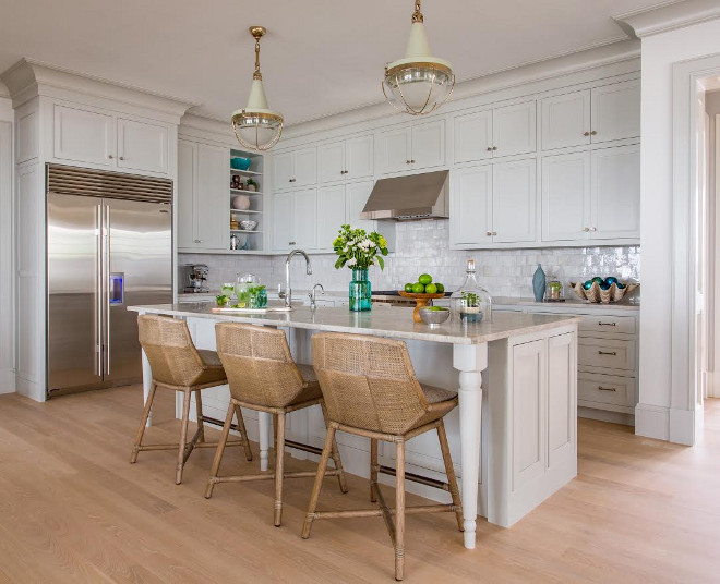 Benjamin Moore Gray Owl Kitchen with Quartzite Countertop. Well-designed kitchens are well laid out for maximum efficiency and flow. They should also feel inviting and have plenty of functional storage. A coastal feel can be found in this kitchen through the choices of color, cabinetry door style, finishes and lighting. Lighting is Malplaquet from Urban Electric. Floors are a white oak with a custom gray stain. #kitchen