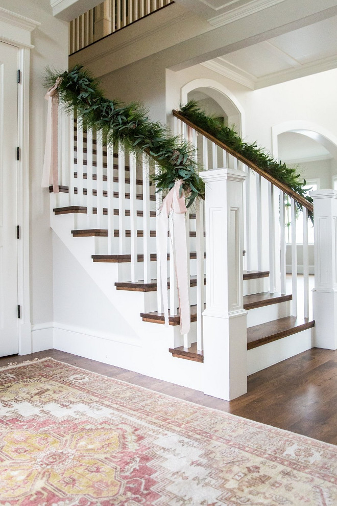 Staircase Christmas Decor. Banister Garland. Make sure you have wire cutters and floral wire to fasten your garland onto the the banister! We like to drape or have the garland follow the line of the banister rather than wrapping it around tightly. We add silk ribbon in our color palette in long bows to soften the look. Staircase Christmas Decor. Banister Garland ideas #StaircaseChristmasDecor #BanisterGarland Studio McGee