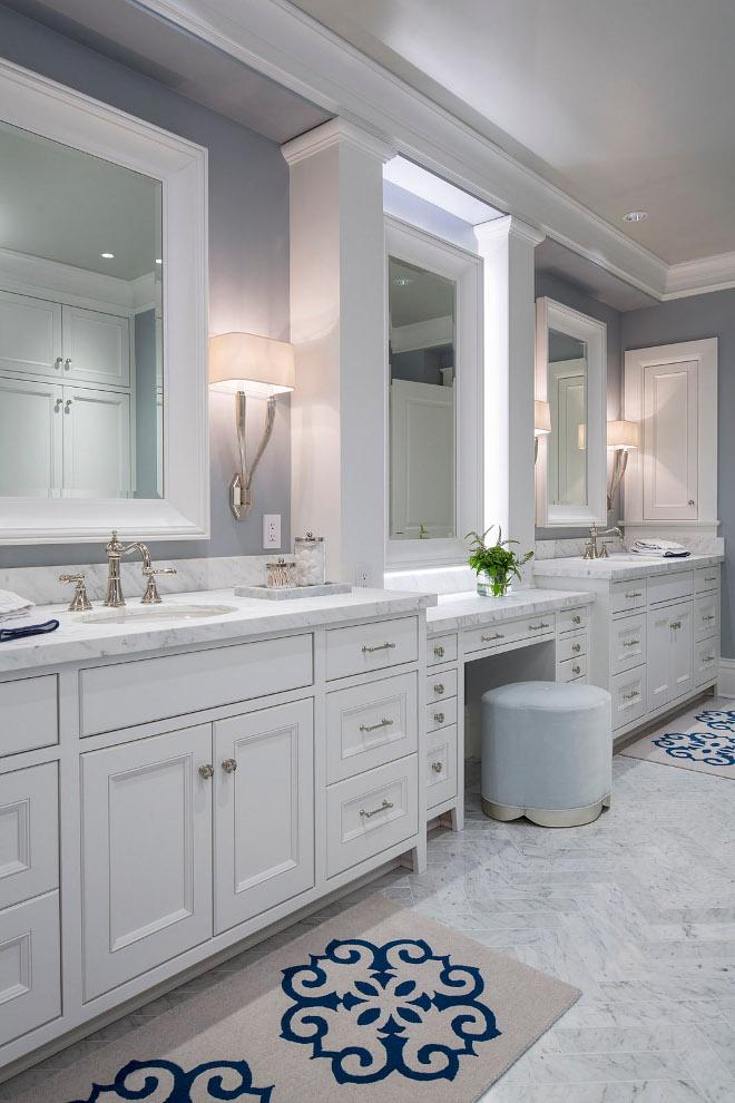 Bathroom make up vanity between sinks. Flooring is marble Bianco Carrara tile in a herringbone pattern. Bathroom make up vanity between cabinets. Bathroom make up vanity between his and hers vanity