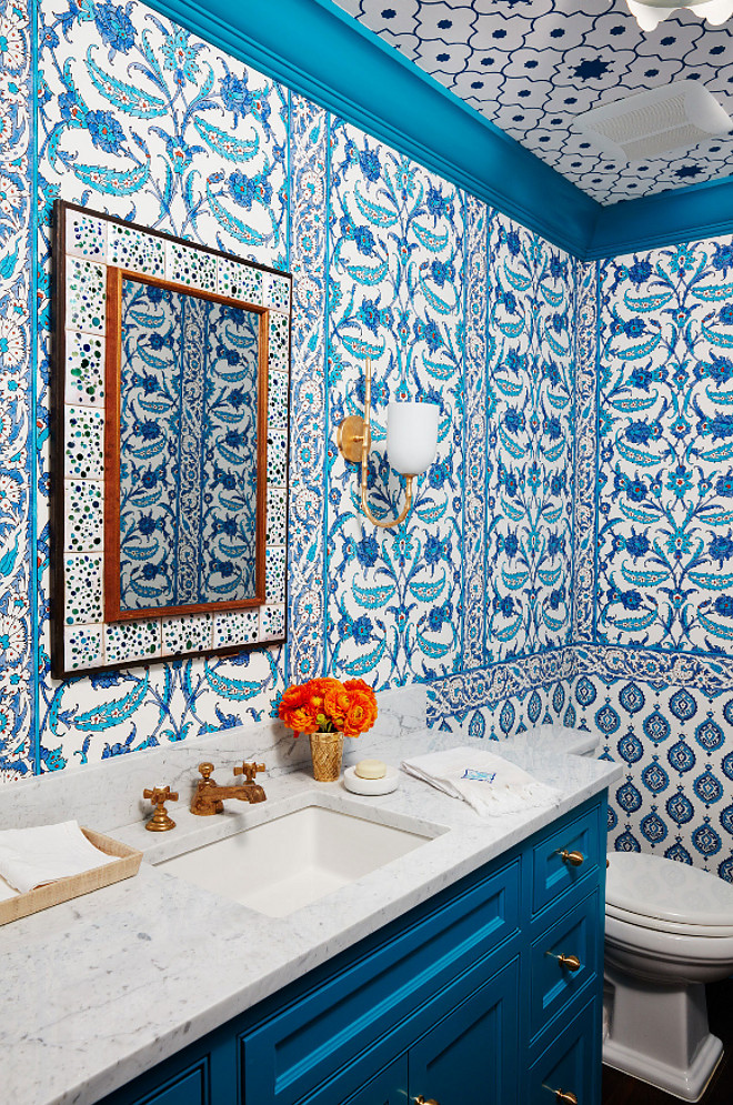 "Bold Blue and White Powder Room. Bold Blue and White Powder Room Ideas. This is what the designer had to say about this space to House Beautiful: "" This windowless powder room under the stairs feels hidden away from everything. Total excuse to go big!"" The space is covered in three blue and white Schumacher wallpapers: Samovar and Topkapi on walls and Taj Trellis on the ceiling. Bold Blue and White Powder Room with blue and white wallpaper and blue vanity. Vanity and trim paint color is ""Benjamin Moore 762 Pacific Palisades"". #blueandwhite #powderroom #wallpaper #BenjaminMoore762PacificPalisades #BenjaminMoorePacificPalisades Andrew Howard Interior Design"