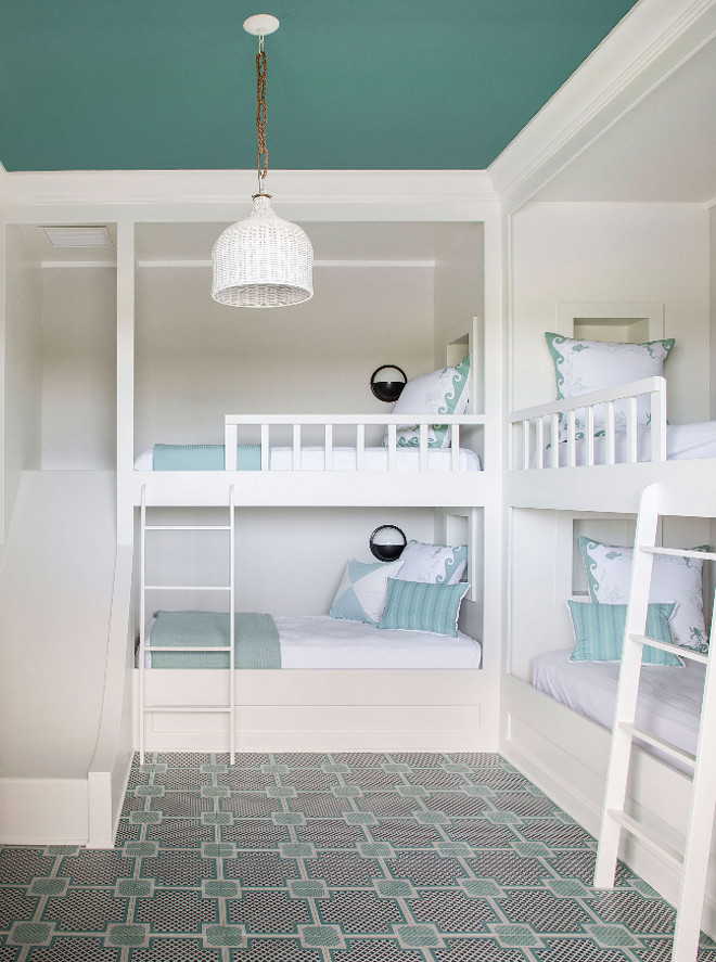 Bunk Room with Four Bunk Beds and Slide. Fantastic bunk room with four custom bunk beds and geometric flooring. The floor is engineered wood tile from Mirth Studio. One of the bunk beds feature a slide. #BunkRoom #FourBunkBeds #BunkBeds #BunkBedSlide Andrew Howard Interior Design