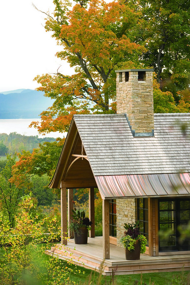 Cabin with shake roof with copper and stone chimney. Stone is Adirondack Buff. The roofing is natural wood red cedar shingles. The roof edge is copper standing seam. #Cabin #shakeroof #stonechimney Roundtree Construction. TruexCullins Architecture + Interior Design