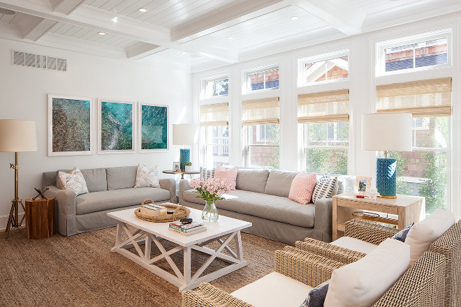 Coastal living room with large chunky jute rug, coffered ceiling, bamboo window shades and pastel colors. Victoria Balson Interiors