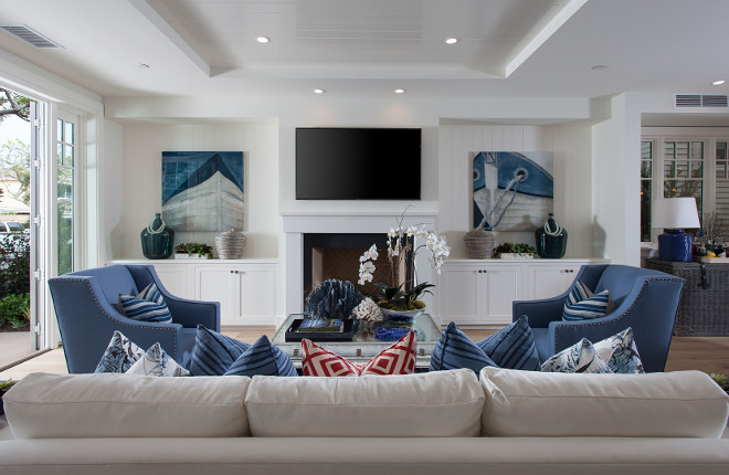 Crisp white living room with blue accessories and built-ins flanking fireplace. Brandon Architects, Inc.