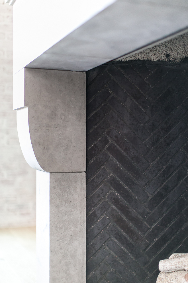 "Dark grey firebrick. A close-up featuring the 1"" x 9"" dark grey firebrick hand laid in a herringbone pattern with the pre-cast limestone surround at the fireplace. #Darkgreyfirebrick #greyfirebrick Patterson Custom Homes"