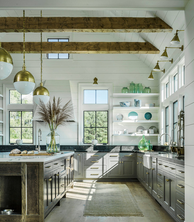Farmhouse kitchen with vaulted ceiling, exposed beams, shiplap walls, shiplap ceiling, black metal windows, grey lower cabinets, open shelves, large oak island, brass cabinet hardware and brass lighting #Farmhouse #kitchen #farmhousekicthen #vaultedceiling #exposedbeams #shiplap #shiplapwalls #shiplapceiling #blackmetalwindows #greylowercabinets #openshelves #oakisland #Brasscabinethardware #brasslighting #farmhouseinteriors #kitchens #kitchen #interiors #interiordesign Roundtree Construction. TruexCullins Architecture + Interior Design