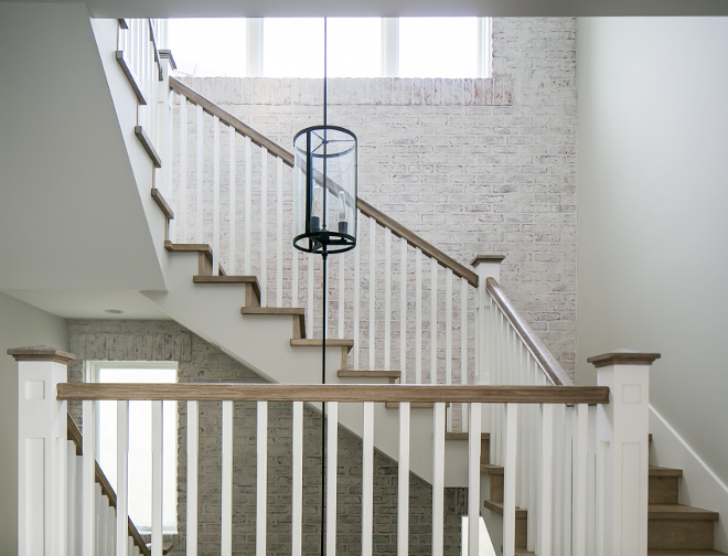 Farmhouse Staircase. Farmhouse staircase. This stairwell packs a serious dramatic punch with its mixed use of materials...including a whitewashed brick wall, stain grade white oak handrail, and custom made brass, three-story chandelier with a pendant at each of the floor's landings. #Farmhousestaircase
