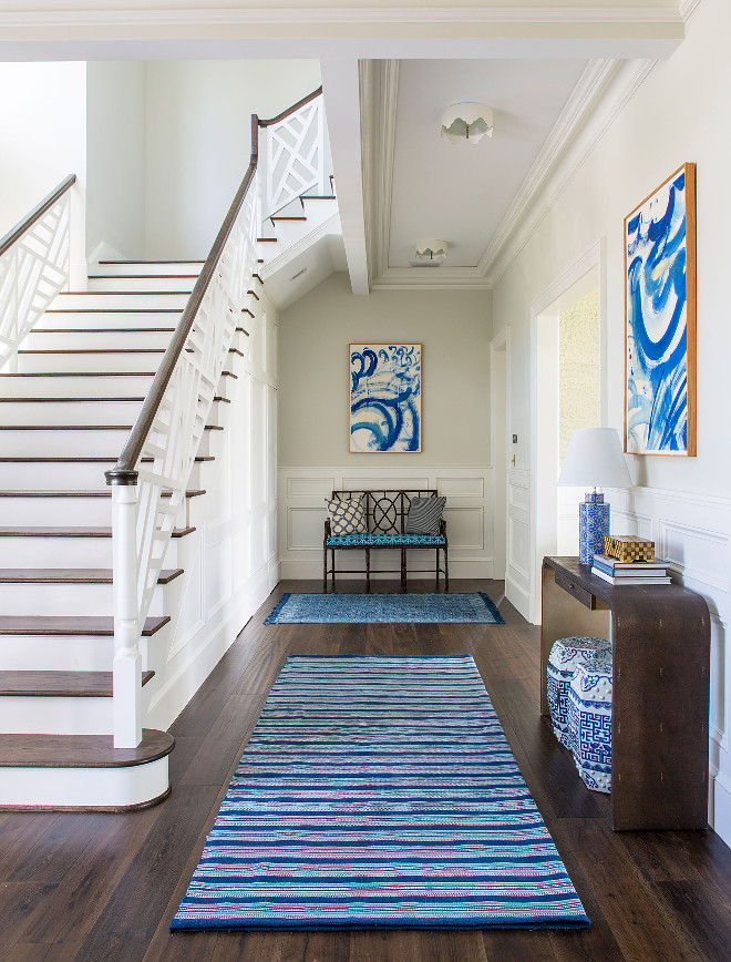 Foyer Wainscoting and Custom Staircase Railing. Beautiful foyer with blue and white decor, dark hardwood floors, wall wainscoting and custom staircase railing. #Foyer #Wainscoting #wallWainscoting #CustomStaircaseRailing #StaircaseRailing Andrew Howard Interior Design