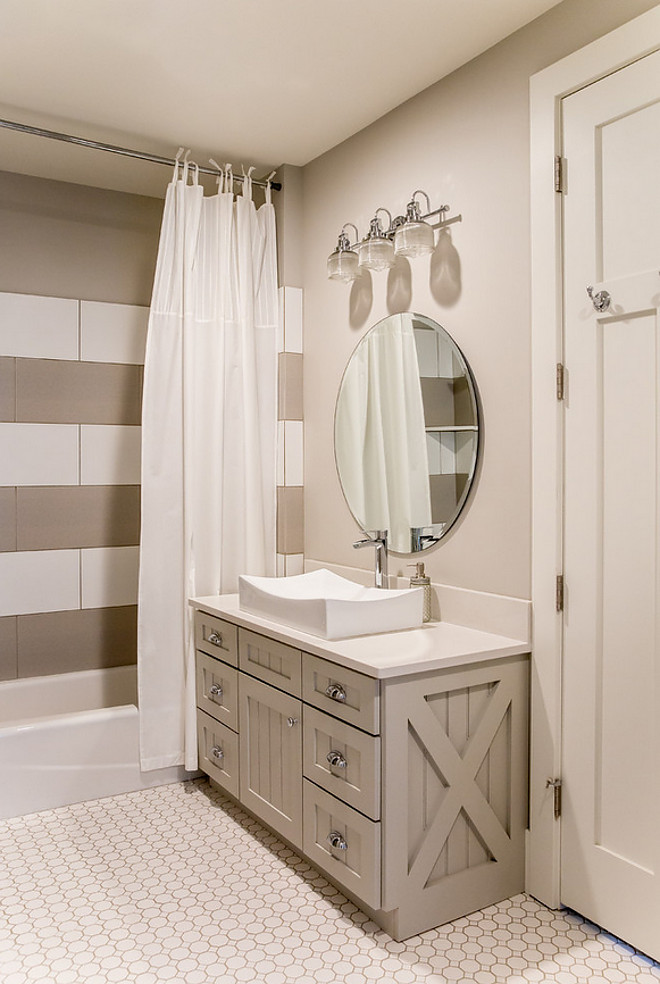 Greige bathroom with grey vanity, white quartz countertop and striped white and grey shower tile. #Greigebathroom #greyvanity #whitequartz #whitequartzcountertop #stripedtiles #whiteandgreytile #showertile Timberidge Custom Homes