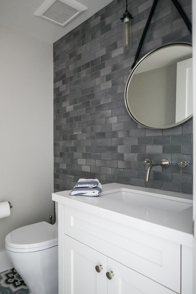 "Grey Wall Tile. Bathroom grey accent wall tile. This beautiful powder room is made complete with a 4""x 4"" charcoal grey Moroccan field tiled accent wall, custom black, grey and blue concrete decorative field tiled floor, mirror from Pottery Barn and Edison Glass Pendants from Restoration Hardware. #GreyWallTile #Bathroom #greyaccentwalltile Patterson Custom Homes"