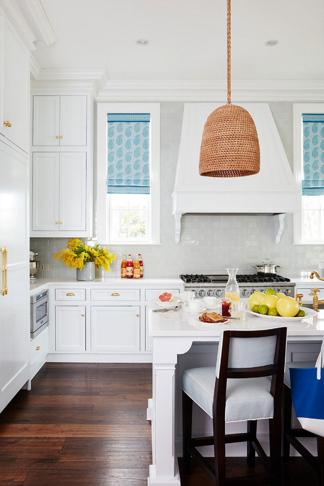 "Kitchen. White kitchen with blue Roman Shades. Kitchens. Cabinets are painted in ""Benjamin Moore White Diamond"". White kitchen Roman Shades. The window shades are done in a Peter Dunham Textiles linen. The rattan pendant is the Green Oaks Pendant by Palecek. #Kitchen #RomanShades #Blueromanshades #Kitchens #BenjaminMooreWhiteDiamond Andrew Howard Interior Design"