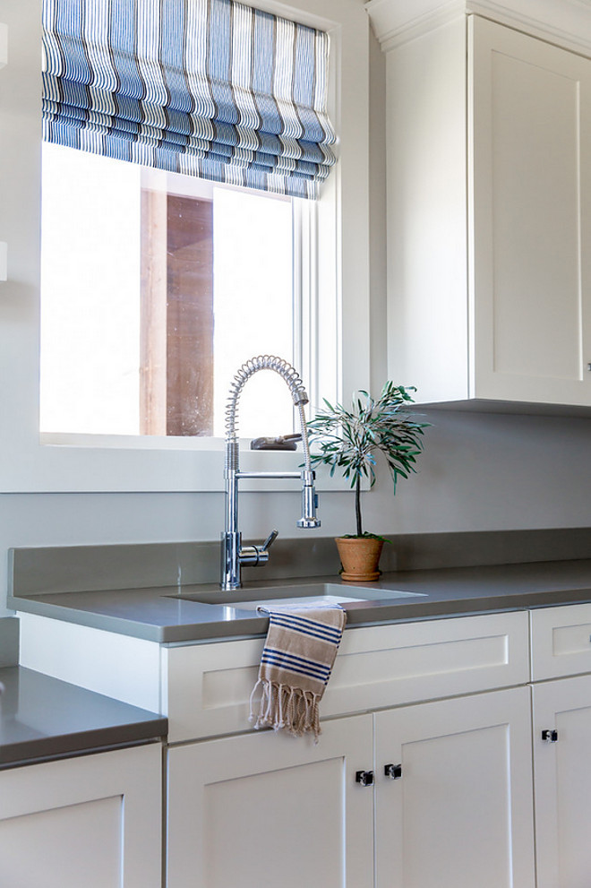 Laundry room with grey quartz countertop, industrial faucet and striped Roman shades. Laundry room. #Laundryroom #greyquartz #countertop #quartzcountertop #industrialfaucet #stripedRomanshades Timberidge Custom Homes