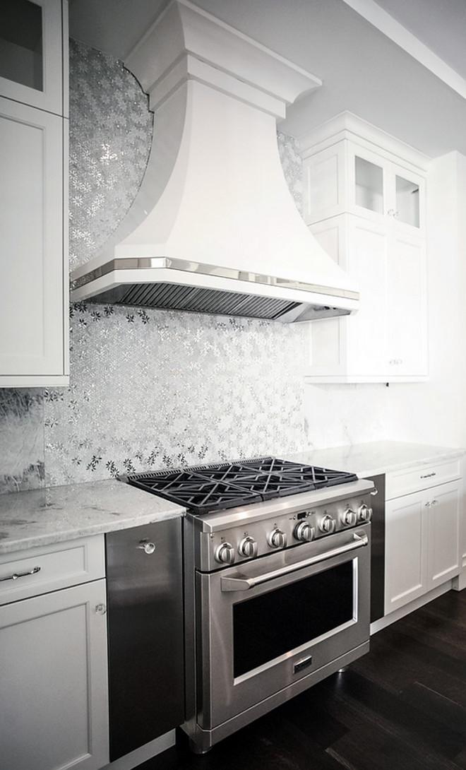 Metallic Backsplash. Kitchen with metallic backsplash tile and white hood with polished nickel inset band. #metallicbacksplash #hood #hoodinset Signature Interior Designs