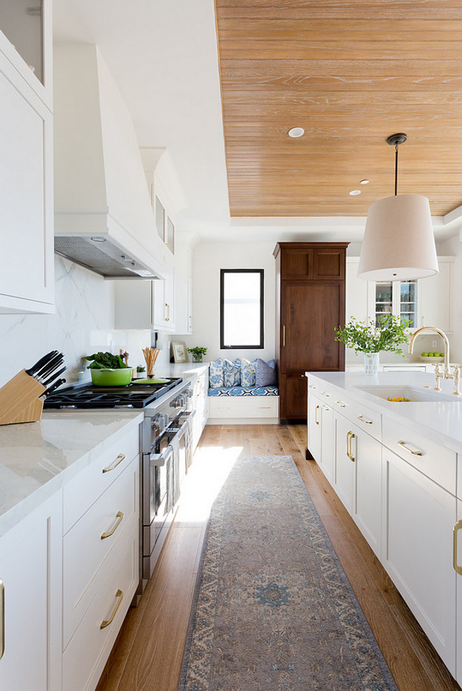 Modern Farmhouse Kitchen. Modern farmhouse kitchen with European White Oak Floors, white oak beadboard ceiling, brass cabinet hardware, black steel windows and a window seat. Wall paint color Baby's Breath by Benjamin Moore. Denton Developments. Amy Bartlam Photography.