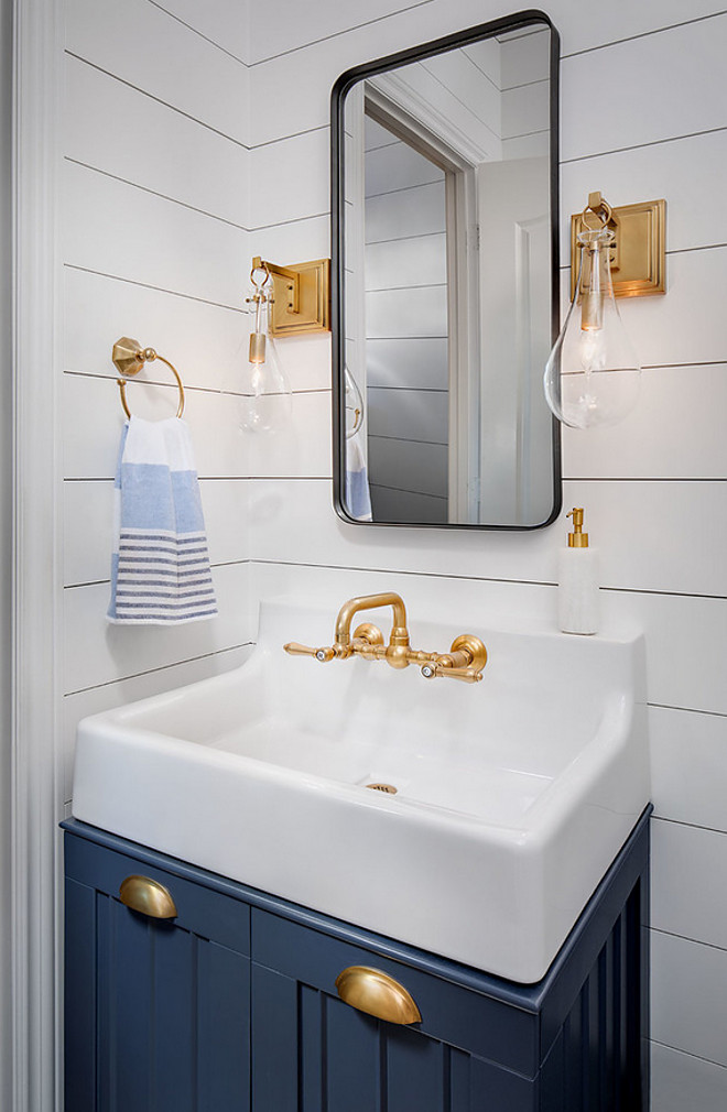 Navy Cabinet with shiplap paneling. Powder room features small navy vanity with matte brass hardware, wall mounted faucet, brass sconces and white shiplap wall paneling. #NavyCabinet #shiplappaneling #Powderroom #smallvanity #navyvanity #mattebrasshardware #mattehardware #wallmountedfaucet #brasssconces #whiteshiplap #shiplapwallpaneling #shiplap #paneling Tracy Lynn Studio