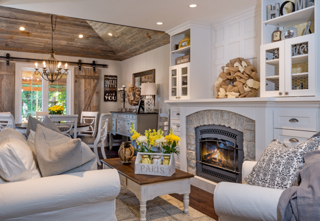 Open concept Farmhouse interiors. This entire space was completely renovated. In the living room, the contractor moved the gas-insert fireplace to make it fit into the layout in a pleasing way. He gave it a new stone veneer surround and crafted built-ins around it, which make it the focal point of the room. The homeowners asked him to fill the cabinet door frames with chicken wire to continue the rustic theme. Open concept Farmhouse interior ideas. Open concept Farmhouse interiors #OpenconceptFarmhouseinteriors #Openconcept #Farmhouseinteriors Hardcore Renos