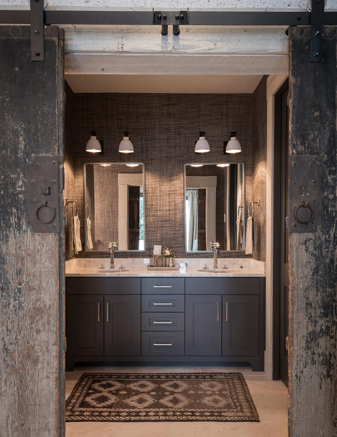 Rustic farmhouse bathroom with reclaimed barn doors, grey natural fiber wallpaper and charcoal grey vanity. #Rusticfarmhouse #farmhouse #bathroom #farmhousebathroom #rusticbathroom #reclaimedbarndoors #greywallpaper #naturalfiberwallpaper #charcoalgreyvanity Locati Architects