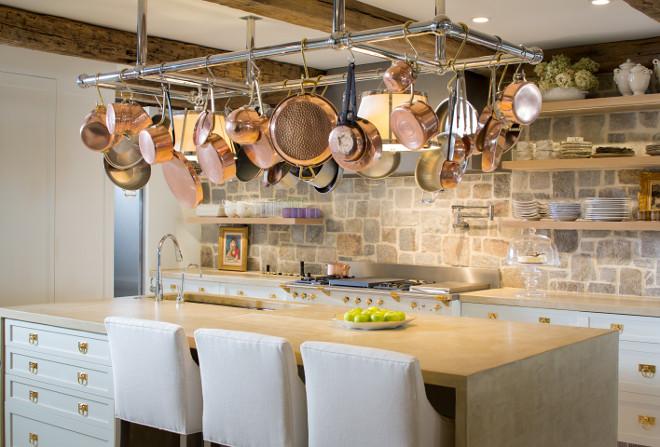 Rustic white kitchen. Rustic white kitchen with concrete waterfall island countertop, custom pot rack, open shelves, rustic reclaimed beams, open shelves and fieldstone backsplash wall. Bayview Builders LLC