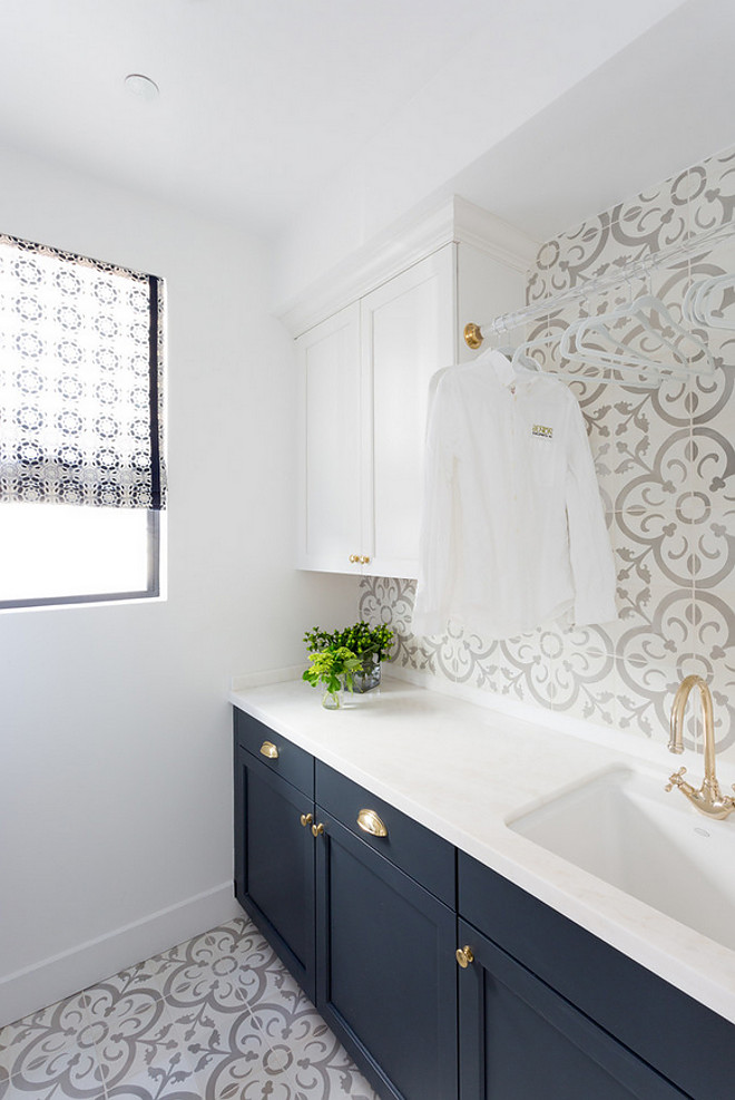 This two-toned laundry room features cabinets painted in white and navy, cement tile flooring, cement tile backsplash and lucite drying rod. #Twotonedcabinet #Twotonedlaundryroom #laundryroomcabinets #whiteandnavytwotonedcabinets #paintcolors #laundryroom #cementtileflooring #cementtile #cementtilebacksplash #lucitedryingrod #dryingrod Denton Developments