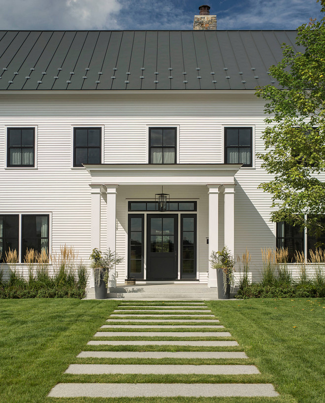 White Farmhouse with black pane windows, black metal roof and black front door. Modern White Farmhouse with black pane windows, black metal roof and black front door #WhiteFarmhouse #Farmhouse #blackpanewindows #blackmetalroof #metalroof #blackfrontdoor #ModernWhiteFarmhouse #blackdoor Roundtree Construction. TruexCullins Architecture + Interior Design