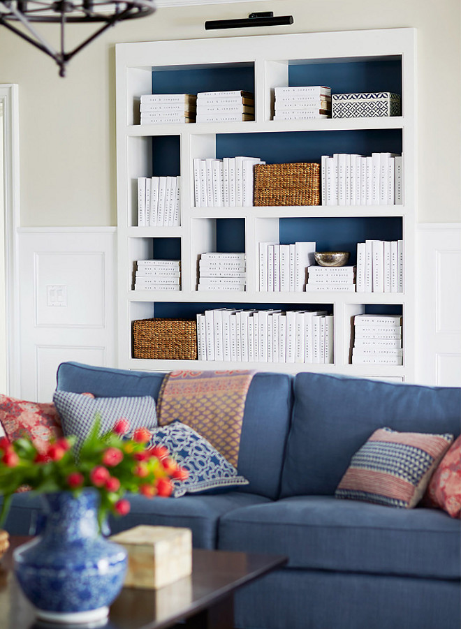 Bookcase painted in navy. The living room also features a white bookcase with back painted in navy, and decorated with woven baskets and white books. #Bookcase #navypaintcolor #whitebooks #bookcasetyling Andrew Howard Interior Design