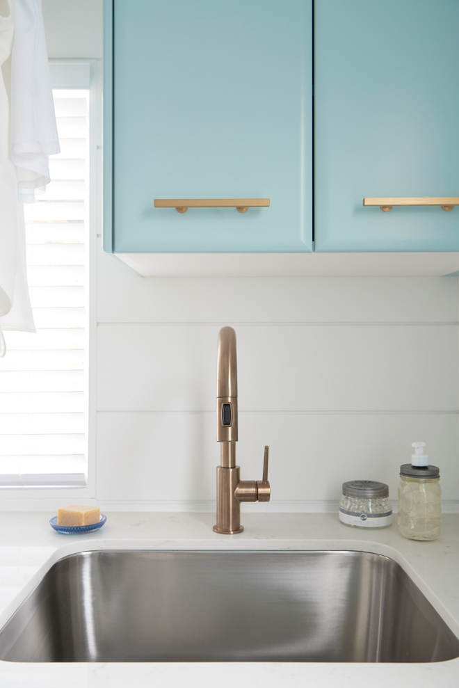 Brass Faucet. Laundry room brass faucet. Faucet is Delta Trinsic Single Handle Pull-Down Kitchen Faucet in Champagne Bronze. A curved stainless steel sink paired with a gold gooseneck faucet is fixed to a white quartz countertop beneath blue laundry room cabinets, painted in Gossamer Blue by Benjamin Moore, accented with brass pulls, and mounted beside a window. #laundryroomfaucet #faucet Soda Pop Design Inc.