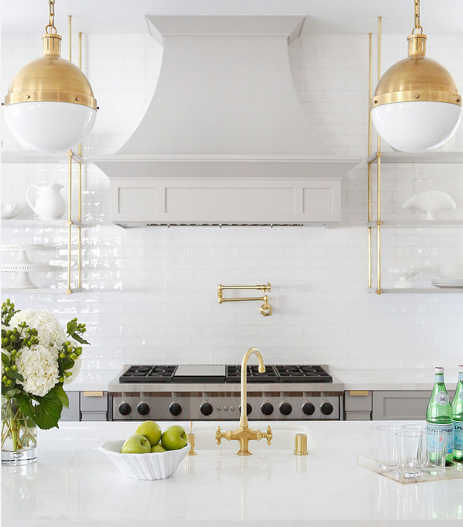 Brass Hicks Pendants. Kitchen feature Brass Hicks Pendants, brass faucet, brass pot filler and brass hardware. The countertops are polished Bianco Namibia. The white walls are a full height tile backsplash. The tile is Beveled white ceramic from Westide Tile. #Brass #HicksPendants #BrassHicksPendants #BiancoNamibia Boswell Construction