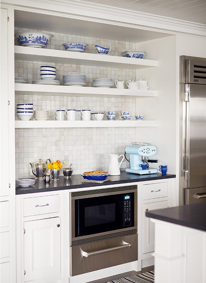 Decorator's White by Benjamin Moore. White kitchen with open shelves and cabinets painted in Decorator's White by Benjamin Moore. The open shelves display pretty blue-and-white dishware. Decorator's White by Benjamin Moore #DecoratorsWhitebyBenjaminMoore Andrew Howard Interior Design
