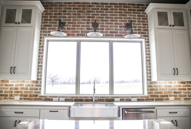 Farmhouse kitchen with barn sconces above windows. Farmhouse kitchen with barn sconces above windows and exposed brick backsplash. Farmhouse kitchen lighting. #Farmhousekitchen #Farmhousekitchenlighting #barnsconces #windowlighting