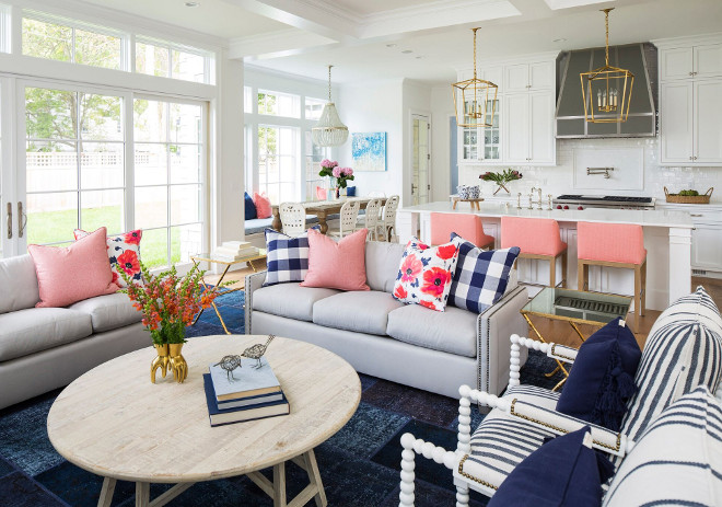 This gray and blue living room features a light gray sofa accented with nailhead trim and blue buffalo check pillows and pink and blue floral pillows. Living room with navy blue rug, open layout, round coffee table, French doors and transoms, pink pillows, checkered pillows and floral pillows #Livingroom #navybluerug #openlayout #roundcoffeetable #Frenchdoors #transoms #pinkpillows #checkeredpillows #floralpillows Martha O'Hara Interiors. John Kraemer & Sons