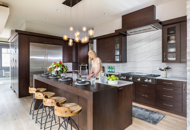 "Modern kitchen design with sleek dark walnut cabinets. Kitchen Perimeter and Island Countertop/Backsplash: Polished 1- 1/4"" White Macaubas Quartzite. Barstools are from Arteriors. Hendel Homes"