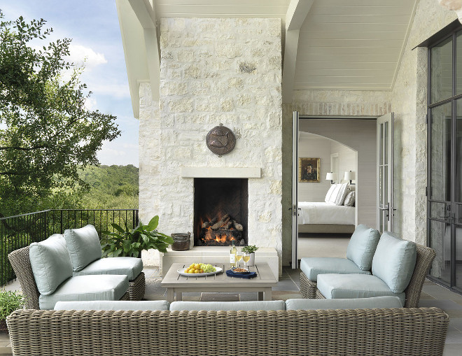 Patio with white stone outdoor fireplace, black steel doors and bluestone floor tile. #Patio #whitestone #outdoorfireplace #blacksteeldoors #bluestonetile #bluestonefloortile #Ryan Street & Associates Greer Interior Design.