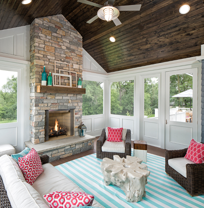 Screened in porch, This summery and cheerful screened-in porch features stained T&G ceiling boards, Cheerful and summery Screened in porch decor ideas, Screened in porch with stone fireplace #Screenedinporch Grace Hill Design