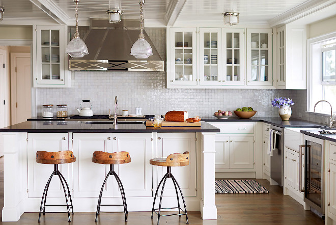 White kitchen painted in Benjamin Moore Decorators White. This Hamptons-style white kitchen also features shaker-style cabinetry, olive knuckle hinges, glazed white terracotta backsplash, custom hardware made from a mold of an antique pull and a gorgeous custom stainless steel range hood. Wall paint color is White Drifts by Benjamin Moore. Trim, ceiling and cabinets are Benjamin Moore Decorator's White. Benjamin Moore Decorators White #BenjaminMooreDecoratorsWhite Andrew Howard Interior Design