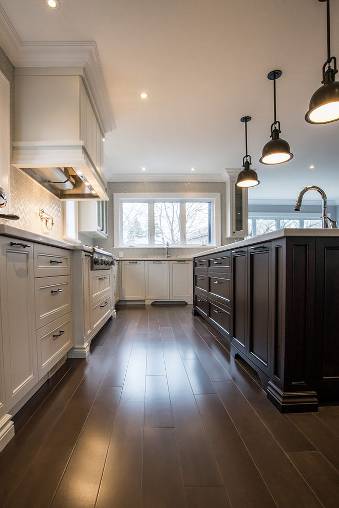 White kitchen with dark stained island and dark stained hardwood flooring. This is a good way to design a warm white kitchen. #whitekitchen #kitchen #darkisland #darkstainedisland #darkhardwood Hardcore Renos