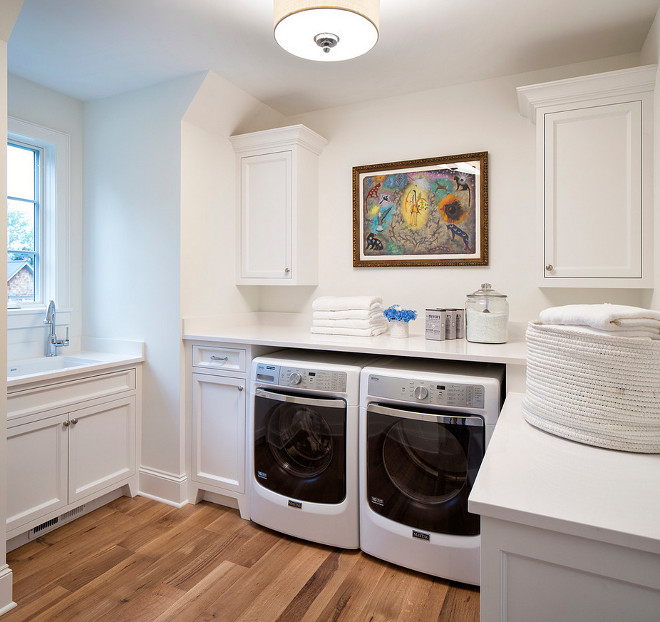 White laundry room painted in Benjamin Moore Chantilly Lace and with white quartz countertop #whitelaundryroom #whitelaundryroompaintcolor #BenjaminMooreChantillyLace Martha O'Hara Interiors. John Kraemer & Sons