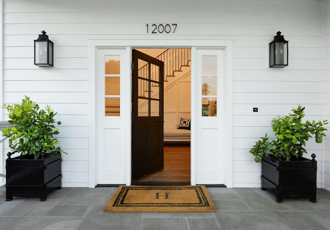 Black Front Door with black planters. Front porch with Bluestone floor tile, black front door with sidelights and black planters. #blackfrontdoor #blackdoor #planters #porch #frontporch #floortile #blueestone Hamilton Architects