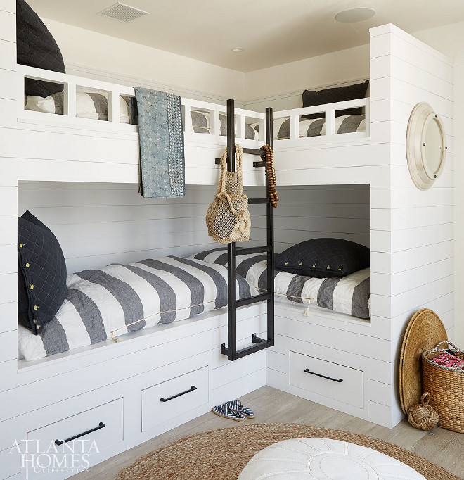 Coastal Farmhouse Bunkroom with shiplap paneling. L-shaped bunkbeds. The bunk room, which sleeps four, features l-shaped bunkbeds, white shiplap siding and coastal-inspired linens. Coastal Farmhouse Bunkroom with shiplap paneling. L-shaped bunkbeds. The bunk room, which sleeps four, features a l-shaped bunkbeds, white shiplap siding and coastal-inspired linens #CoastalFarmhouse #CoastalFarmhouseinteriors #CoastalFarmhouseBunkroom #FarmhouseBunkroom #Coastalbunkroom #shiplap #shiplappaneling #Lshapedbunkbeds #bunkroom #bunkbedssleepsfour #bunkbeds #shiplap #shiplapsiding