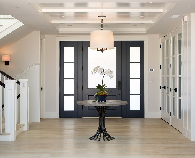 Crisp Foyer design with navy blue front door with frosted glass, beadboard ceiling and white oak hardwood flooring #Foyerdesign #navyblue #frontdoor #frostedglass #whiteoak #hardwoodflooring Christian Rice Architects, Inc