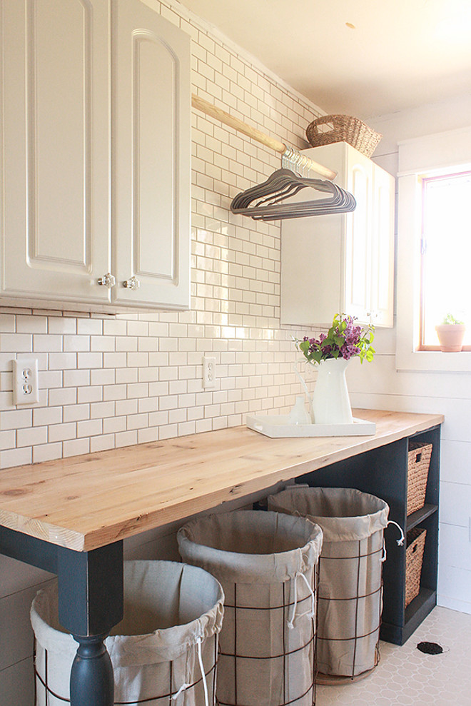 Farmhouse Laundry Room. Gorgeous farmhouse laundry room with diy folding table with butler's block countertop, diy shiplap walls and white subway tile backsplash. Farmhouse Laundry Room. Farmhouse Laundry Room Design. Farmhouse Laundry Room. Farmhouse Laundry Room #FarmhouseLaundryRoom #Farmhouse #LaundryRoom Twelve On Main