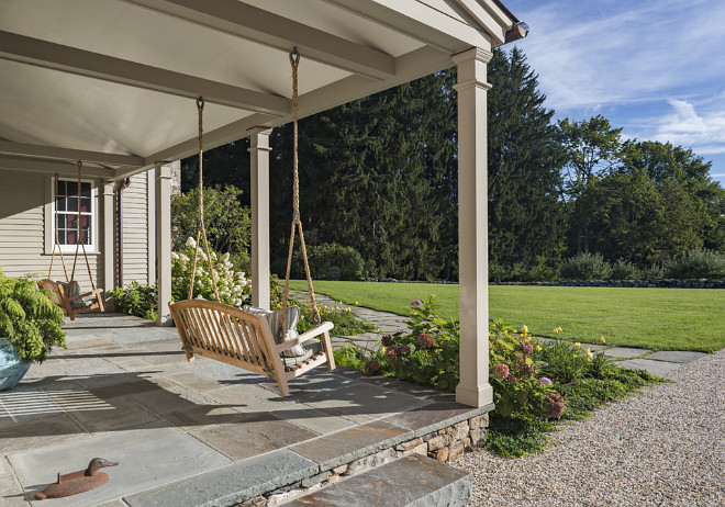 Front Porch with two swings, The entrance porch is paved in bluestone and features twin swings #porchswing #porch #swing