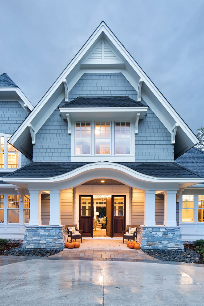 Grey Shingle Home with White Trim and Grey Stone Porch columns, The exterior is grand and inviting with an eyebrow arch over the covered front porch, Home exterior design Grey Shingle Home with White Trim and Grey Stone Porch columns #GreyShingleHome #WhiteTrim #GreyStone #Porchcolumns Grace Hill Design