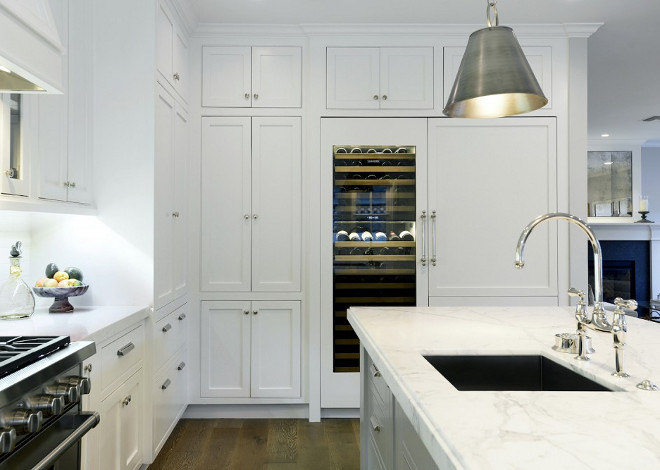 Kitchen Wine Cooler. Kitchen features white cabinets with white marble countertop and built in glass-door wine cooler #kitchen #winecooler Hamilton Architects