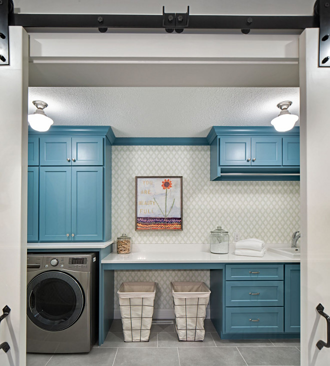 Laundry room with barn doors, blue cabinets, metal laundry hampers and wallpaper The wallpaper is Thibaut wallpaper - Bonaire T88755 Color Green on White #Laundryroom #barndoors #Bluecabinets #metallaundryhampers#laundrybaskets #wallpaper Grace Hill Design