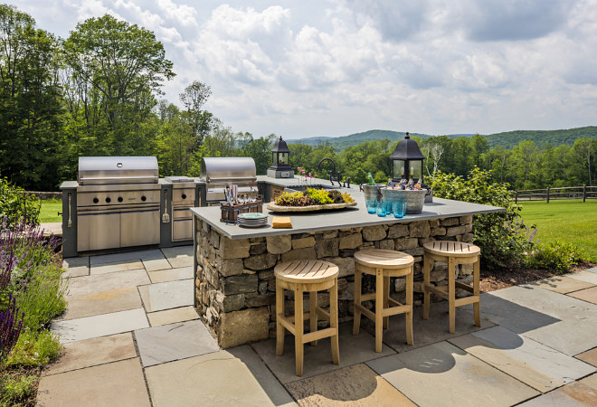 Outdoor kitchen The outdoor kitchen features fieldstone walls with bluestone counters and copper lanterns #Outdoorkitchen Haver & Skolnick LLC Architects