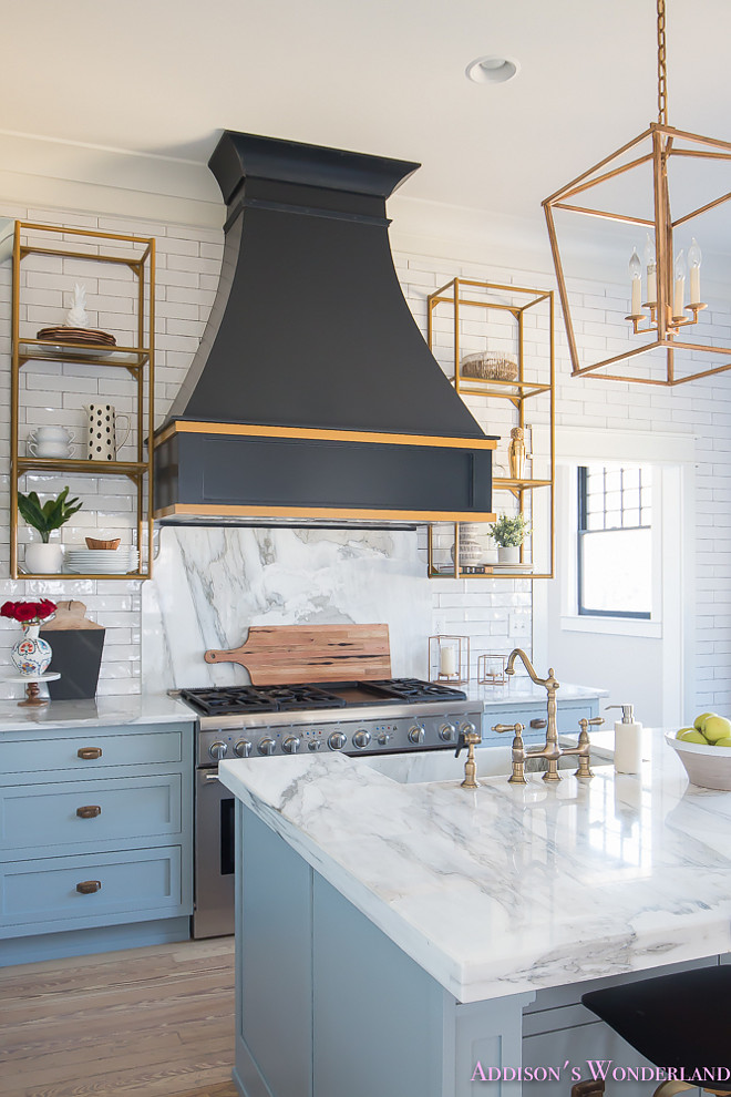 A black French kitchen hood, painted in Sherwin Williams Inkwell, is accented with gold trim and it's flanked by brass shelving. #blackhood #Frenchhood #Frenchkitchenhood #SherwinWilliamsInkwell #hoodgoldtrim Home Bunch's Beautiful Homes of Instagram @addisonswonderland