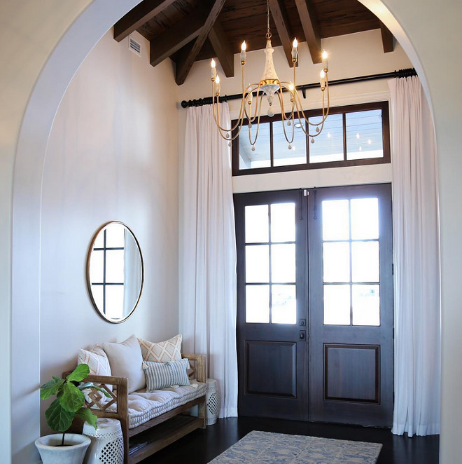Arched Foyer with Double Wood Front Doors with draperies, Chandelier, Bench, Dark Hardwood floors and exposed ceiling beams. Bench and chandelier is Gabby Decor. Mirror is by Wisteria. #ArchedFoyer #Foyer #DoubleWoodFrontDoors #DoubleFrontDoors #Foyerdraperies #draperies #Chandelier #Bench #DarkHardwoodfloors #Hardwoodfloors #exposedceilingbeams #beams Old Seagrove Homes