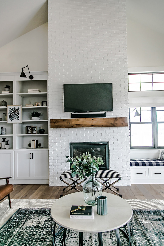 Farmhouse Brick Fireplace. The painted brick fireplace is the focal point of the family room. Warmth was introduced into the space with the addition of a custom made white oak mantel. The mantel was given a custom stain, which compliments the other wood tones in the home. #FixerUppper #MagnoliaMarket #Farmhousestyle Sita Montgomery Interiors
