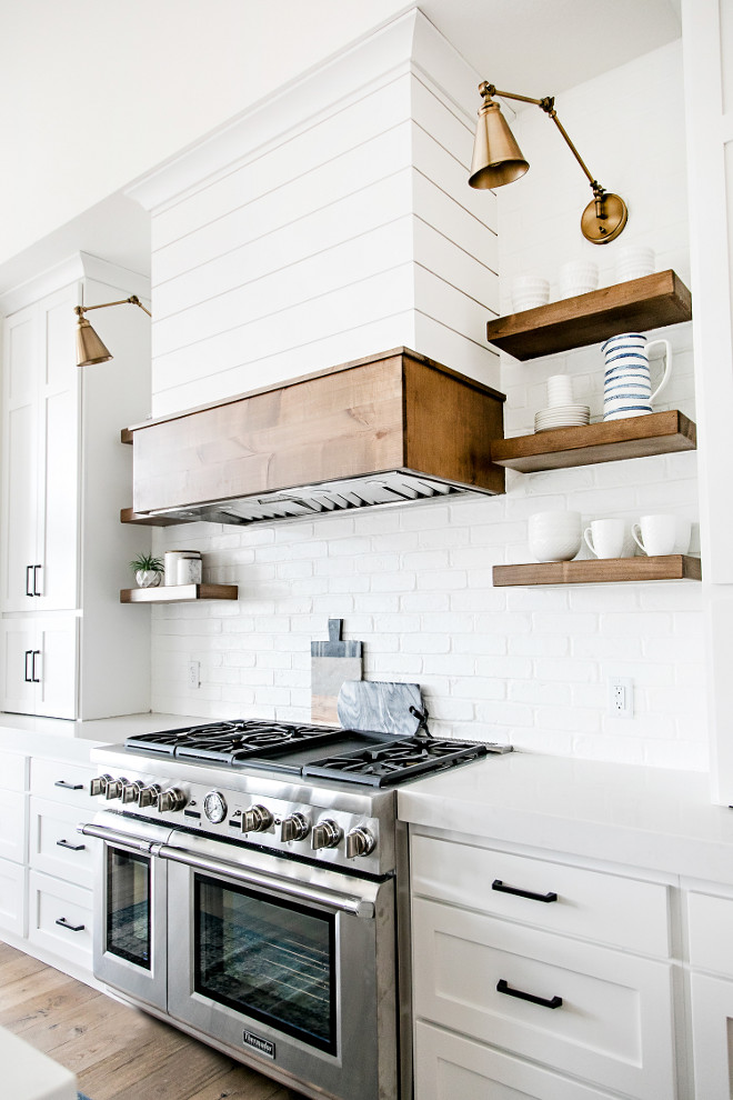 Farmhouse Kitchen Brick Backsplash Chunky Floating Open Shelves and Shiplap Hood. The white shiplap kitchen hood got a dose of stained wood and the open shelving was made of stained wood as well. The warm wood elements pop against the white shiplap and painted brick backsplash. Farmhouse Kitchen Brick Backsplash Chunky Floating Open Shelves and Shiplap Hood. Farmhouse Kitchen Brick Backsplash Chunky Floating Open Shelves and Shiplap Hood #FarmhouseKitchen #BrickBacksplash #ChunkyFloatingOpenShelves #ChunkyShelves #FloatingOpenShelves #ShiplapHood #Shiplap Sita Montgomery Interiors