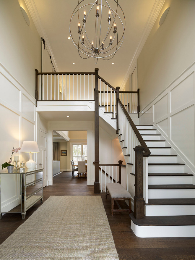 "Foyer. A beautiful two story entry with large iron openwork globe and classic candleholder lights is welcoming and beautiful. Rift and quarter sawn oak flooring adds to the richness and warmth of this home. The Orb is from Restoration Hardware and the overall dimensions are 40.5 diameter and 43"" H. #Foyer Knight Architects LLC"